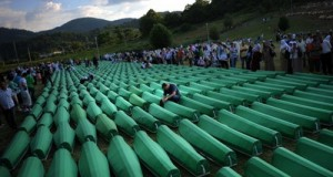 Bosnians mourn over coffins of newly identified victims of the 1995 Srebrenica massacre during the preparation for a mass burial at the Potocari memorial cemetery near Srebrenica on July 10, 2010. More than 775 bodies found in mass grave sites in eastern Bosnia will be reburied on 15th anniversary of the Srebrenica massacre. Nearly 8,000 men and boys from the enclave were captured and systematically killed by Bosnian Serb forces in the days after the fall of Srebrenica on July 11, 1995. The victims were shot and interred in mass graves, then reburied haphazardly later in more than 70 sites in a bid to cover up the evidence.    AFP PHOTO / DIMITAR DILKOFF (Photo credit should read DIMITAR DILKOFF/AFP/Getty Images)