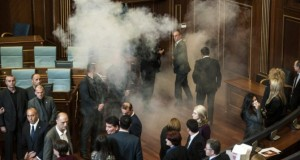 Members of the Parliament disperse after a tear gas was launched by opposition lawmakers, in the Kosovo's parliament in Pristina, on November 17, 2015. Kosovo's opposition fired tear gas and pepper spray in parliament on November 17 while protesters outside threw stones and paint, in the latest eruption of a long-running protest against agreements made with Serbia. AFP PHOTO/ARMEND NIMANI
