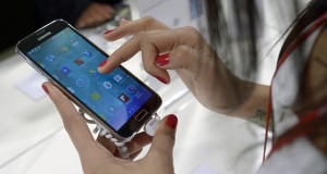 FILE - In this Feb. 25, 2014 file photo, the Samsung Galaxy S5 is demonstrated at the Mobile World Congress, the world's largest mobile phone trade show in Barcelona, Spain. Smartphones, tablets and other gadgets aren't just changing the way we live and work. They are shaking up Silicon Valley's balance of power and splitting up businesses.  (AP Photo/Manu Fernandez, File)
