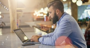 Side view. Young bearded businessman wearing blue shirt,sitting at table in cafe and using laptop.On desk is smartphone and cup of coffee. Man browsing internet on computer. Freelancer checking email.