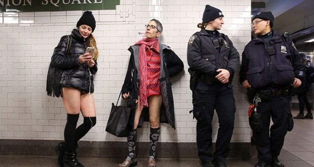 """People participating in the annual """"No Pants Subway Ride"""" stand next to law enforcement officers at Union Square in the Manhattan borough of New York City, U.S., January 13, 2019.  REUTERS/Caitlin Ochs"""